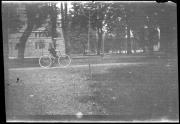 Man riding bicycle past Bosler Hall, c.1890